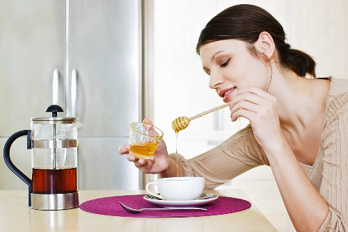 Young woman sweetening her tea with honey