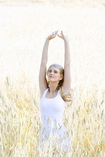 Blond woman, stretching, standing in a cornfield