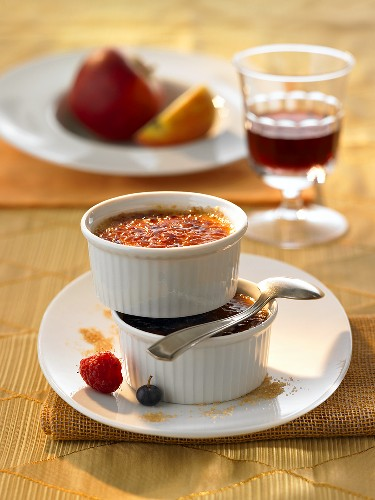 Two dishes of crème brûlée with dessert wine