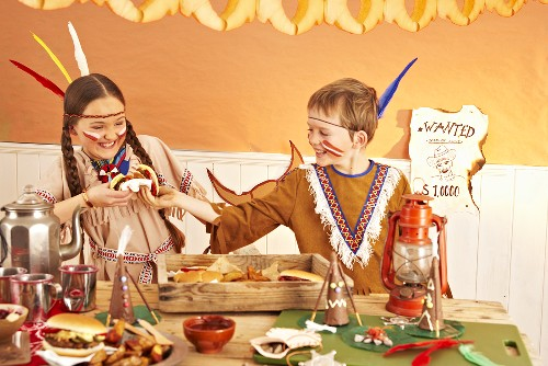 Two children dressed as Indians fighting over a hamburger at a party