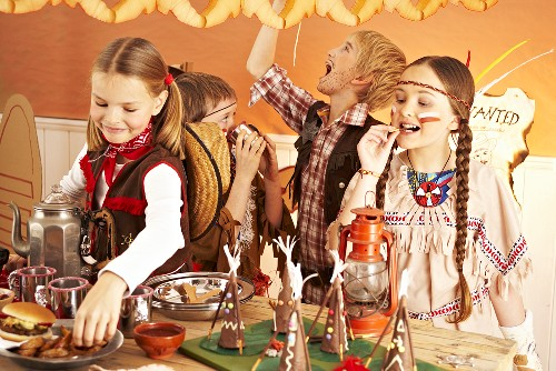 Four children dressed as cowboys and Indians at a party buffet