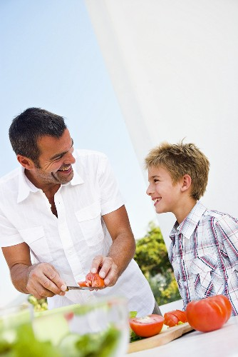 Father and son preparing salad out of doors