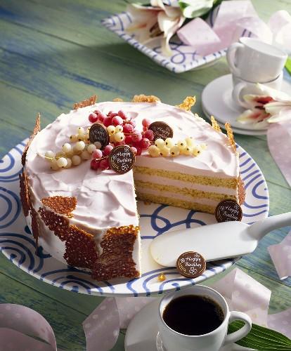 Orange birthday cake with red- & white currants & brittle