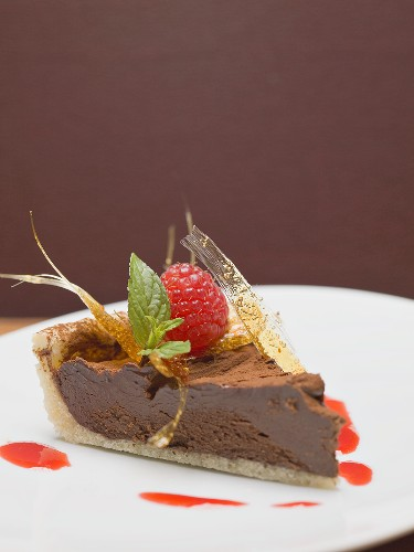 Piece of chocolate tart with a caramel fan and a raspberry