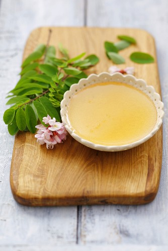 Acacia honey in a small dish with acacia blossom and leaves