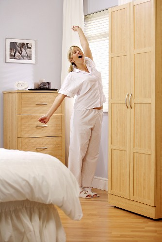 Woman in pyjamas yawning and stretching in bedroom