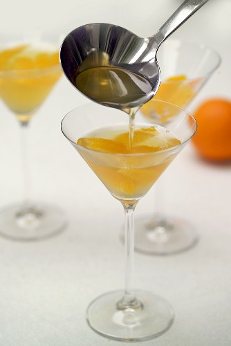 Putting orange jelly into glasses