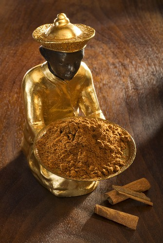 Gilded statuette with bowl of ground cinnamon, cinnamon bark