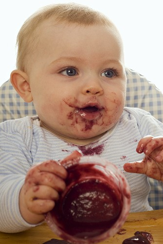 Messy baby with fruit compote