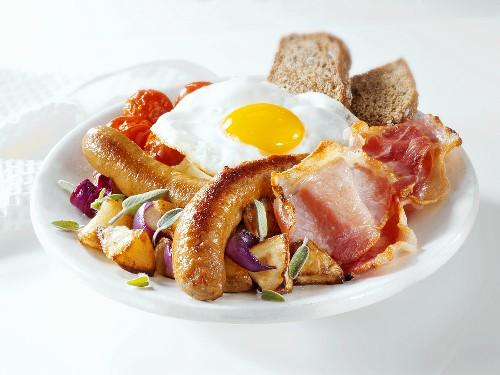 English breakfast: sausages, bacon, egg, potatoes, tomatoes