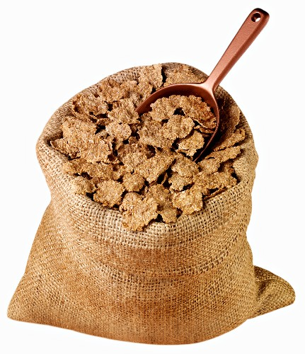 Whole-grain wheat flakes in jute sack with scoop