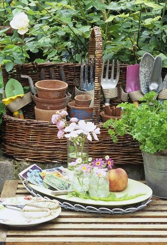Still life: flowers, basket of terracotta pots & garden tools