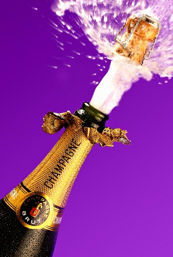 Cork flying out of champagne bottle, purple background