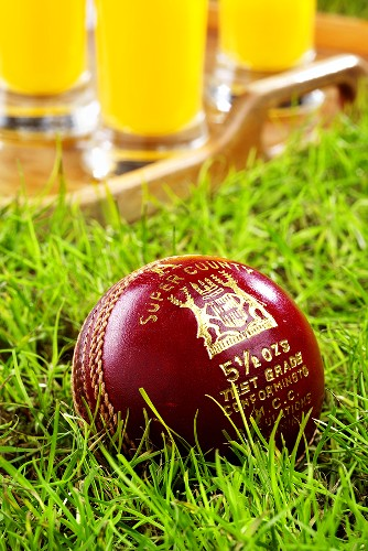A cricket ball in grass, tray of orange juice behind