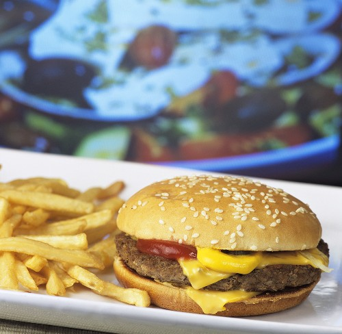 Hamburger and chips in front of television screen