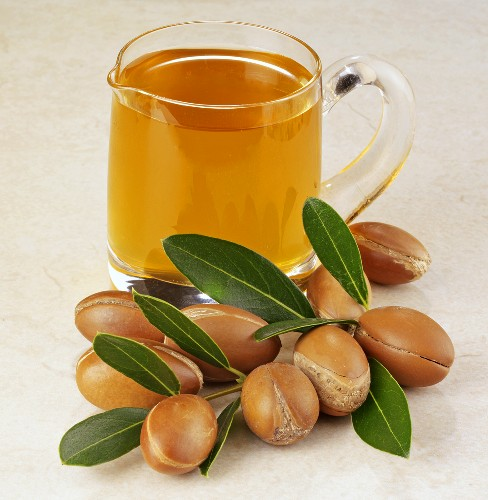 Twig with argan nuts and small jug of argan oil