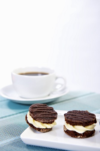 Chocolate biscuits filled with cream and a cup of coffee