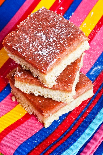 Rhubarb bars, stacked, on a striped cloth