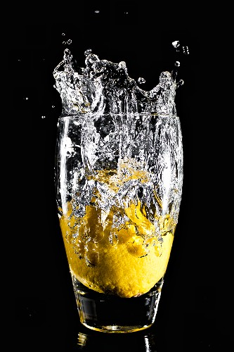 A whole lemon falling into a glass of water