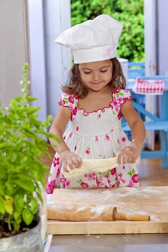 Small girl kneading dough