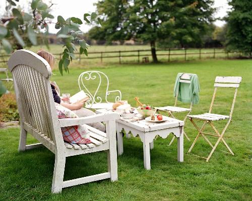 Brotzeit auf Gartentisch, Frau liest ein Buch