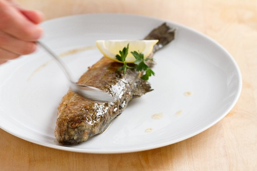 Fried trout being drizzled with melted butter