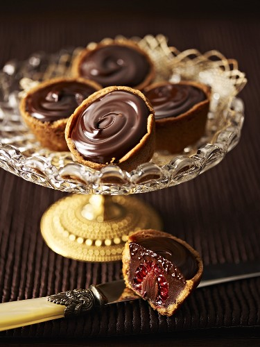 Raspberry cakes with chocolate cream on an elegant cake stand