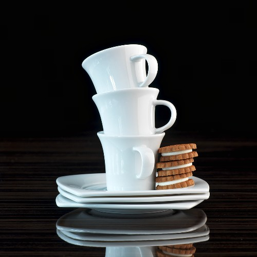 A stack of espresso cups with three espresso biscuits