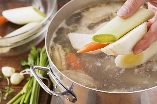Gemüse zum Suppenhuhn geben