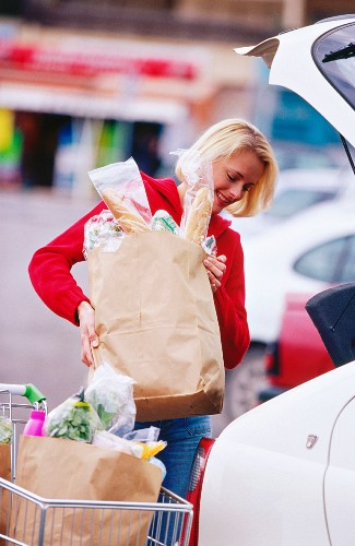 Young woman loading food shopping into car
