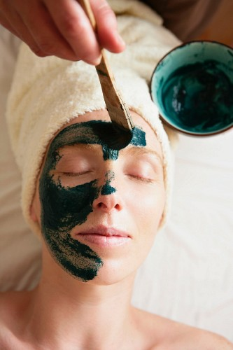 Green mud being applied to a woman's face