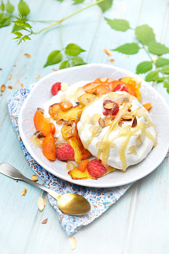 Pavlova with grilled almonds,caramel,roasted apples,apricots and raspberries
