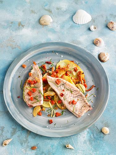 Bauchfleisch vom Thunfisch auf Kartoffeln mit Tomaten und Zwiebeln