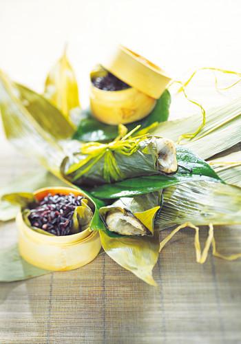 Wolfsbarsch im Bananenblatt, gedämpfter schwarzer Reis