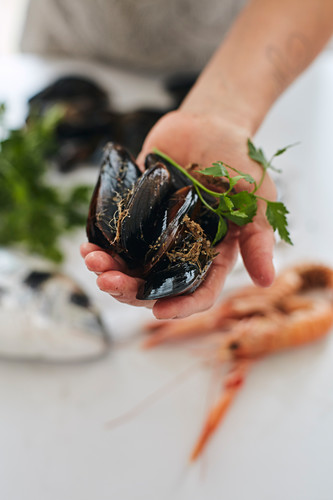 Fishmonger presenting mussels to a customer