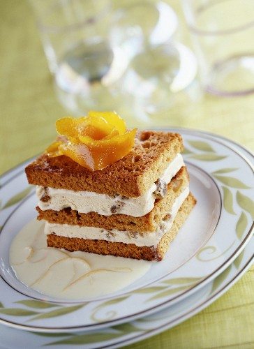 Layered chilled gingerbread and cream dessert with orange sauce