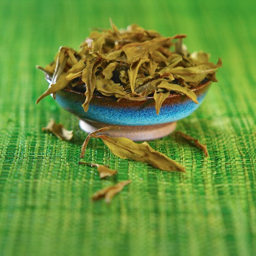 Dragon Well tea (Chinese green tea) in bowl on green mat