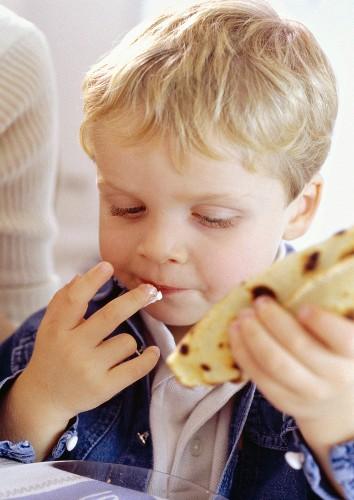 A little boy eating a crêpe