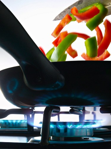 Cooking peppers in a frying pan on a gas cooker