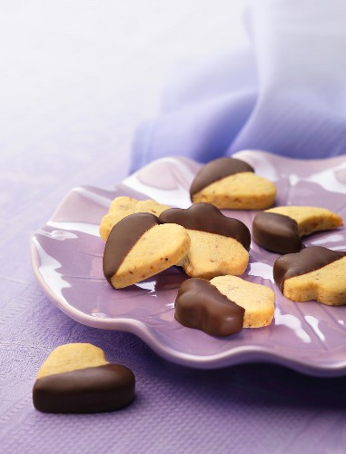 Heart, moon and star-shaped cookies partly coated in chocolate