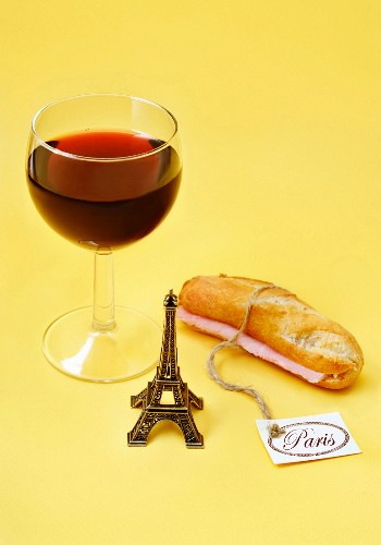 Composition with a mini Eiffel Tower,a glass of red wine and a ham sandwich
