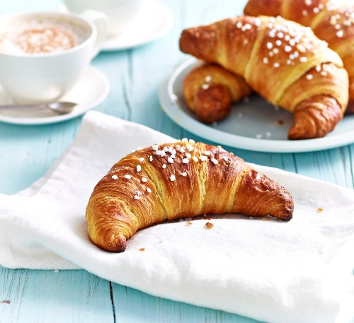 Croissants sprinkled with crystallized sugar and a cup of cappuccino