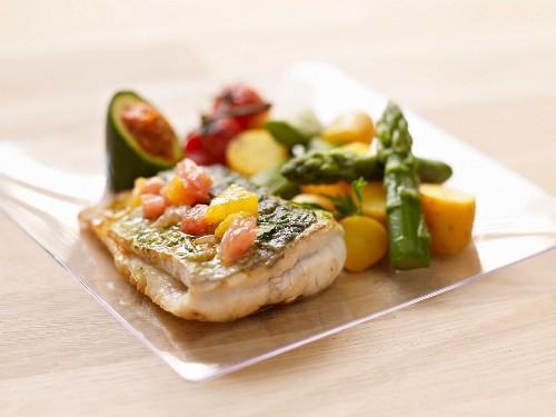 Piece of sea bass with citrus fruit, asparagus-potato salad and stuffed zucchini