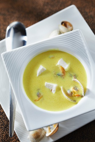 Coconut milk-turmeric consomme with cockles and cream and haddock cubes