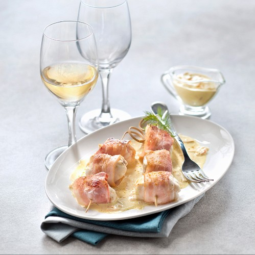 Fish skewer with smoked bacon and curry sauce, glass of white wine