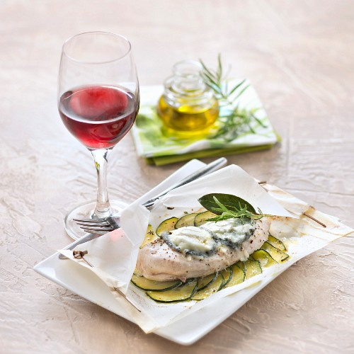Hähnchenbrust mit Zucchini und Rosmarin im Pergamentpapier und ein Glas Rotwein