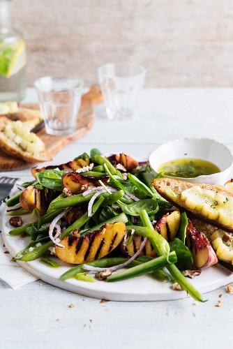Goat's cheese bruschettas, green bean, spinach, walnut and grilled nectarine salad