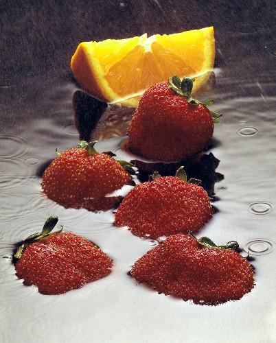 Fresh Strawberries and Orange Wedge in Water