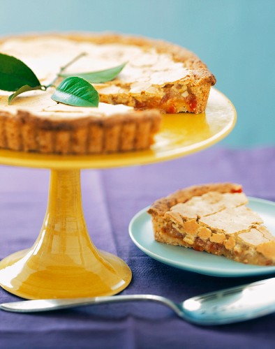 A Hot Pepper Tart on a Stand with a Slice on a Plate