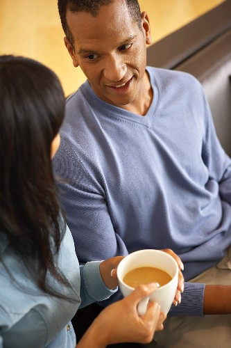 Woman with cup of coffee beside man on sofa